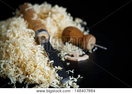 Woodworking tools. Chisel with sawdust on a black background.