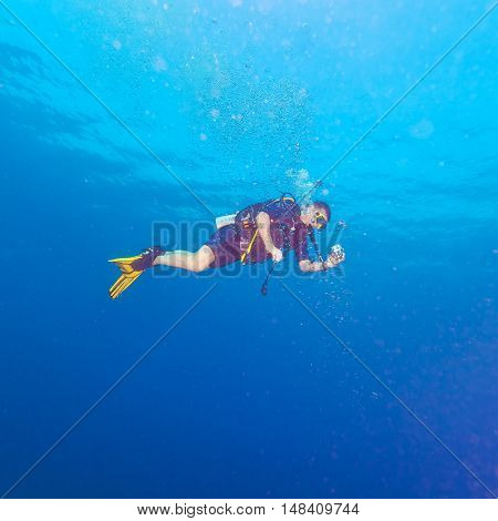 Diver with bright yellow fins and underwater camera