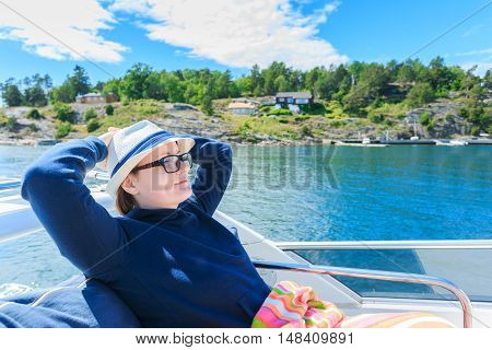 Relaxed girl with closed eyes of pleasure sitting on sailboat enjoying mild sunlight fashion model in luxury sea cruise summer vacation and travel