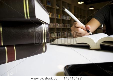 Woman Reading Book In Library.