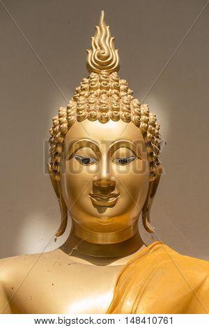 closeup face of ancient golden Buddha's image