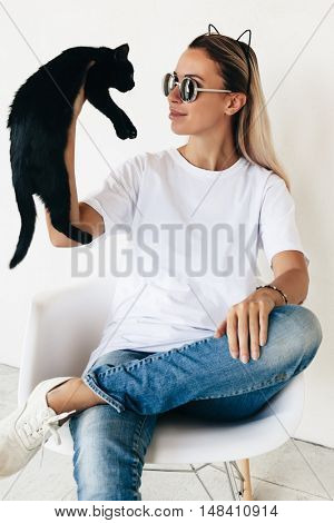 Woman wearing blanc t-shirt, jeans and sneakers sitting on chair and playing with black kitten, toned photo, front tshirt mockup on model, hipster style