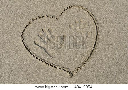 Handprints and heart drawn on wet sand