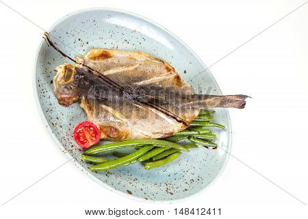 dry fish on plate with asparagus and tomatoes isolated on white