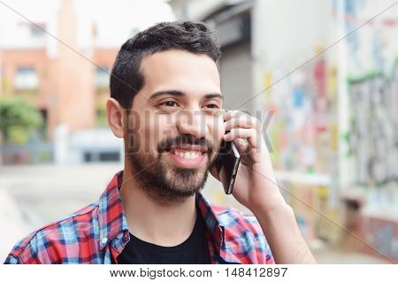 Handsome young latin man talking on the phone. Trendy and urban scene.