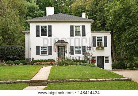 White Stucco House with Backyard Woods