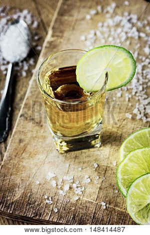 Tequila shot with lime and salt on vintage wooden background.
