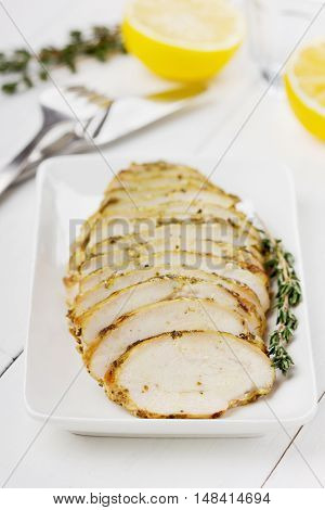 Chicken fillet slices with thyme on a white plate.