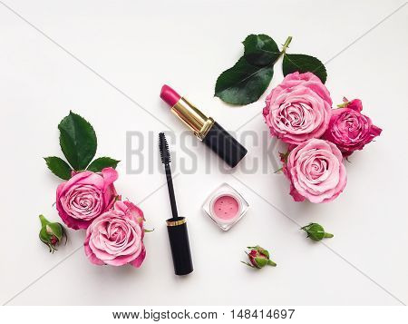 Decorative flat lay composition with mascara lipstick and blush decorated with flowers. Top view on white background view from above