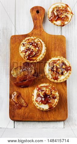 Tartlets from ricotta cheese with nuts and caramel apple. Top view, flat lay.