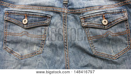 Blue denim jean pants back pockets with buttons texture fabric close up modern urban lifestyle background with empty copyspace casual style clothing fashion for woman, man, teenagers