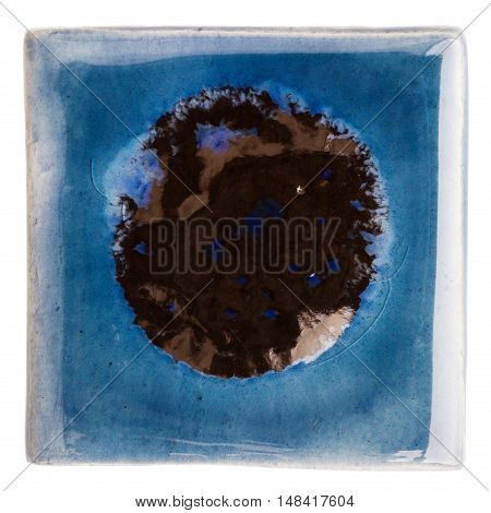 Blue handmade glazed ceramic tile with big black dot in middle isolated on white