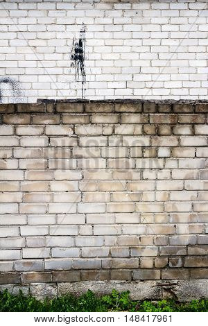 Old weathered wall of bricks with a splash of black tar