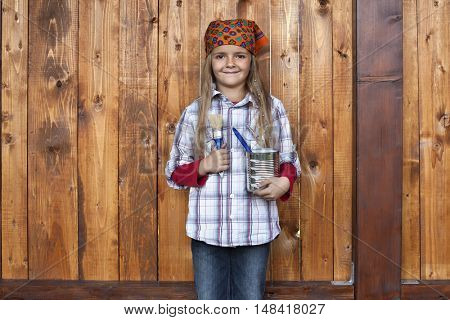 Happy girl painting the wood shed - standing in front of wooden wall