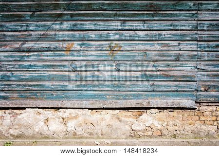 Peeling blue paint on weathered wood wall