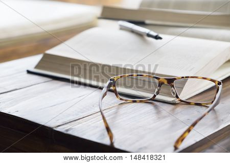 glasses on open book in library or cafe