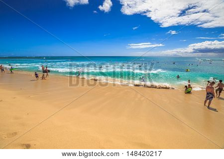 Waikiki, Oahu, Hawaii - August 27, 2016: Body boarding is a popular water sport in Waikiki area. One of best places to board is near the Waikiki Pier at Queens Surf Beach, a section of Waikiki Beach.