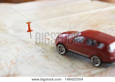 Travel concept background.Red pushpin push point of location destination on map with blured red car