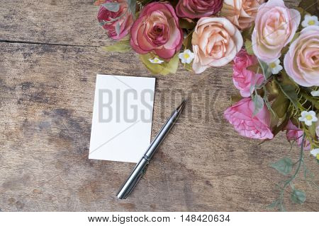 Vintage background empty note pen and flowers on wooden background. Copy space for your text