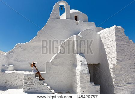 Female in white dress sits at the stairs of the Paraportiani Church of Mykonos, Greece
