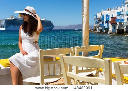 Elegant woman in white sits at the waterfront of Little Venice in Mykonos, Greece