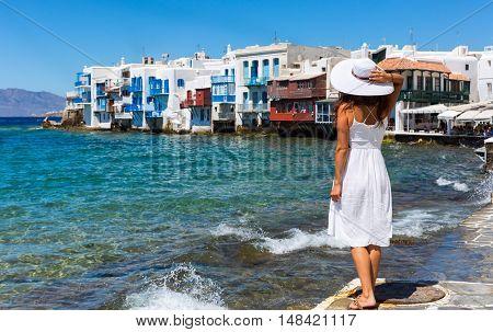 Woman in white dress is watching the scenery of Little Venice on Mykonos island, Greece