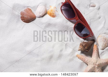 Topview summer background. Sand beach with a lot of seashells and starfish red sunglasses. Vintage tone Retro filter effect Soft focus Low light.(selective focus)