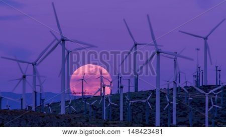 Many wind turbines in the desert with full moon