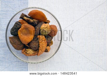 Cup of dried fruits on the blue and white weave cloth background