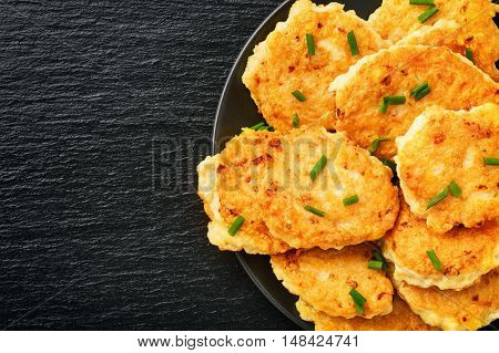 Roasted chicken cutlets with garlic and cheese on black background.