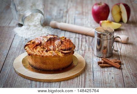 Layered apple pie on vintage, wooden table with baking utensils