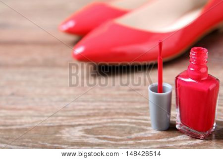 red nail polish with female shoes behind
