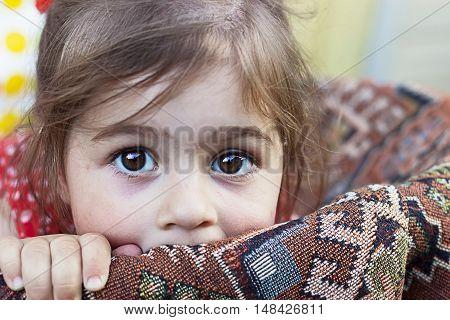 Portrait of cute sad little girl outdoors
