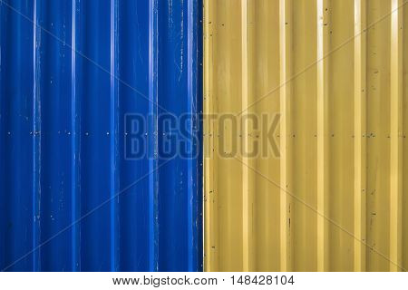 Background of blue and yellow corrugated iron fence.