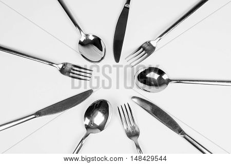 Silver cutlery forks knifes and spoons are around in circle on white background.