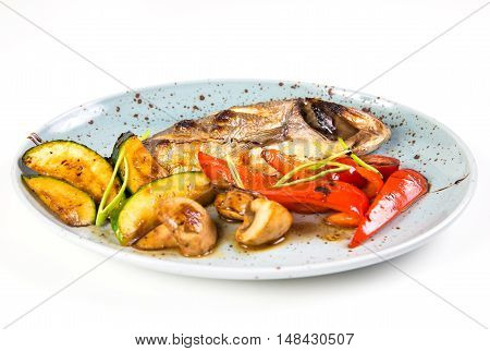 grilled fish on plate with grilled vegetables isolated on white