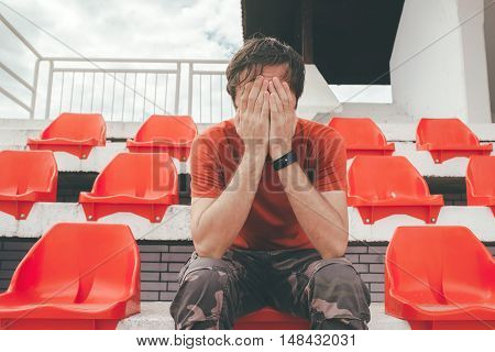 Disappointed man at sport stadium watching the game in disbelief while his team is losing the match