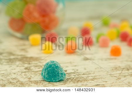 Colorful jelly beans on the wooden background. Focus on foreground