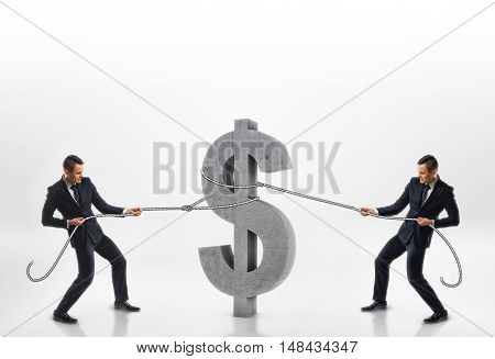 Two businessmen pulling big concrete 3d dollar sign with ropes in opposite directions isolated on white background. Rivalry and competition. Emulous workmates. Colleagues and associates.