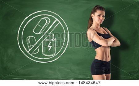 Cropped portrait of fitness girl on the background of a blackboard with a sign that prohibit dry protein and pills. Healthy lifestyle. Nutrients and vitamins. Fitness and sport.