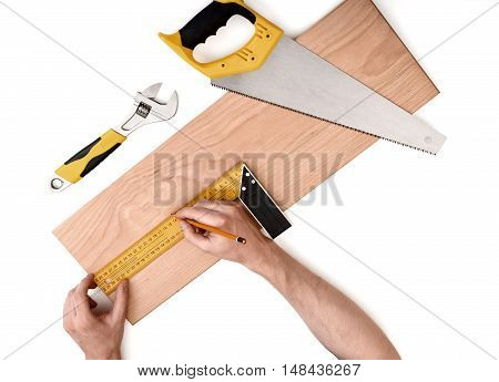 Close up view of a man's hands measuring wooden plank with iron ruler with angle bar with adjustable wrench and a handsaw near it isolated on white background. Tools and instruments.