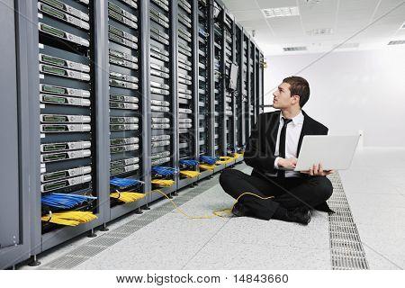 engenheiro jovem homem de negócios com laptop fina de alumínio moderna na sala de servidores de rede