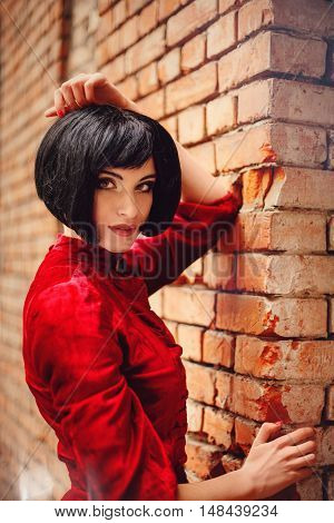 Young brunette girl in vintage romantic red dress near the old brick wall. Fairy tale nostalgic mood. Warm tinted