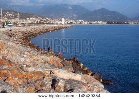Vacationers people and fishermen on a stone jetty in the harbor of Alanya near the lighthouse. Turkey.