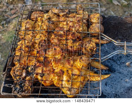 Appetizing fried chicken pieces on the grill on the grill