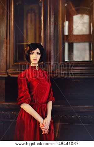 Portrait of lady brunette in the rich interior on the wooden cupboard background. Beauty girl brunette with hairstyle and makeup in red vintage dress with brooch. Fairy tale nostalgic mood. Added photo filter and grain/noise.