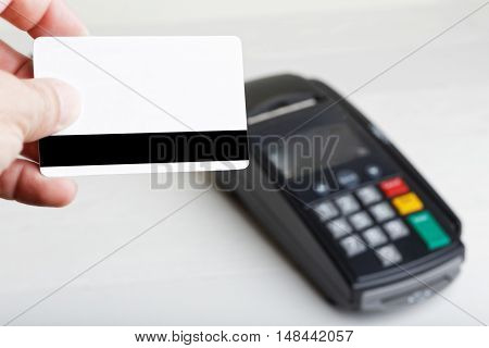 Mockup of a plastic card in the hand and payment terminal on blurred background. Copyspace.