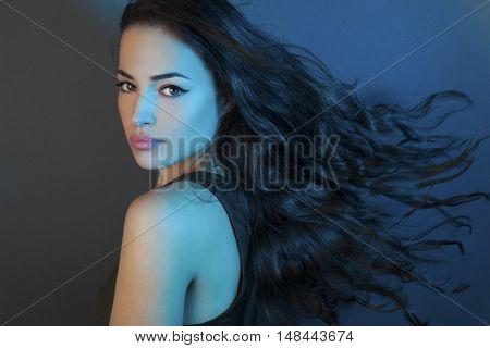 beautiful girl with long flying hair studio blue light