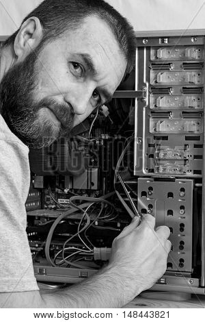 fixing computer. a man with a beard repair the system unit. black and white photo