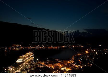 A view of the Kotor Skyline in Montenegro at night. Showing the glow of buildings and boats on the water.